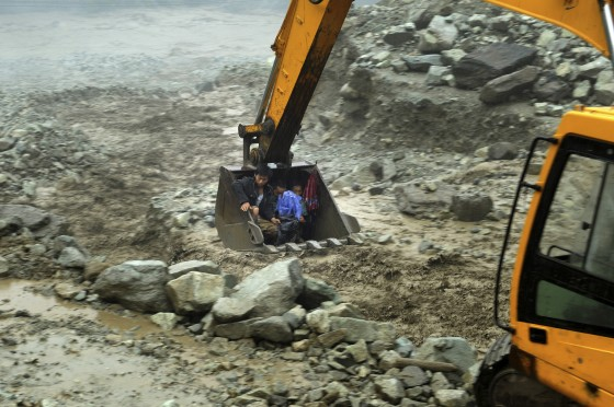 An excavator moves villagers away from a flooded area during heavy rainfall in Yingxiu