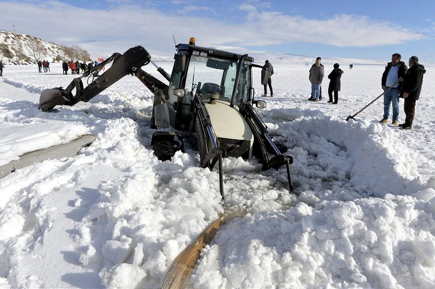 Yüzeyi donmuş Çıldır Gölü üzerinde kar temizleme çalışması yapan iş makinesinin bir bölümü, buzun yumuşak olduğu kısımda suya battı. ( Günay Nuh - Anadolu Ajansı )